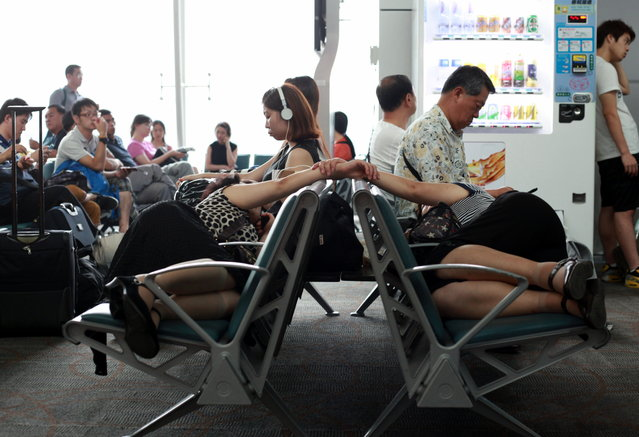 """""""Twins (or not) Sleeping in the waiting area"""". I was waiting for my flight to Seoul North Korea and then I saw these two women sleeping on the benches in the waiting area. Nobody near them seemed to be paying attention though! I can't see their face but I wanna know if they are twins or not. They have identical dresses, body shapes, and even hair. Why are they holding hands? To make sure they do not get separated from each other? Photo location: Guangzhou Airport, Guangzhou, China. (Photo and caption by Serious Pigeon/National Geographic Photo Contest)"""
