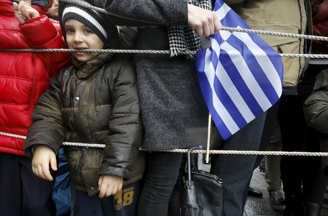 A boy stands behind crowd control ropes as Greeks waving flags stand under the rain to watch a military parade during Independence Day celebrations in Athens March 25, 2015. Thousands of Greeks braved heavy rainfall on Wednesday to watch the Independence Day parade in front of the parliament after being banned in previous years for security reasons. (Photo by Yannis Behrakis/Reuters)