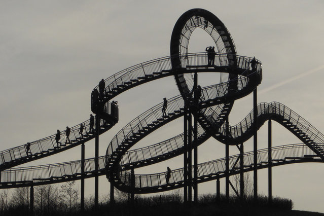 """People can be seen walking on the """"Tiger and Turtle Magic Mountain"""" art installation in Angerpark, Duisburg, Germany on December 267, 2018. Designed by Ulrich Genth and Heike Mutter in 2011, it is 21 meters tall, made out of tin, zinc and steel. It resembles a roller coaster but is completely walkable, except for the loop. (Photo by Jan Scheunert/ZUMA Wire/Rex Features/Shutterstock)"""