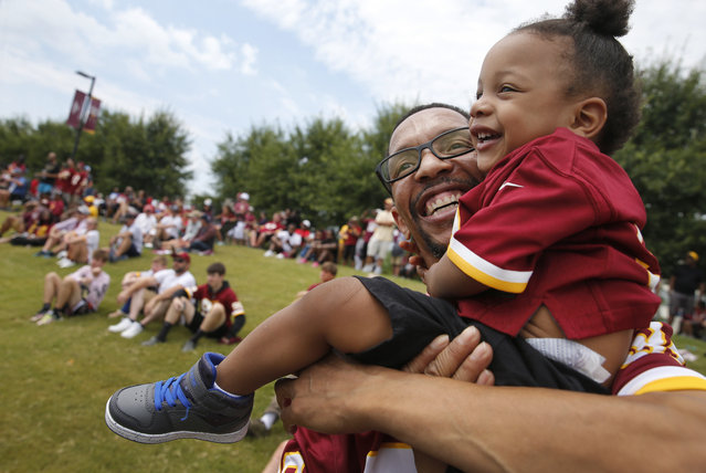 Calvin Richardson, with son Calvin, 18 months, of Wilmington, Del., watch the Washington Football Team's NFL training camp Saturday, July 31, 2021, in Richmond, Va. (Photo by Dean Hoffmeyer/AP Photo)