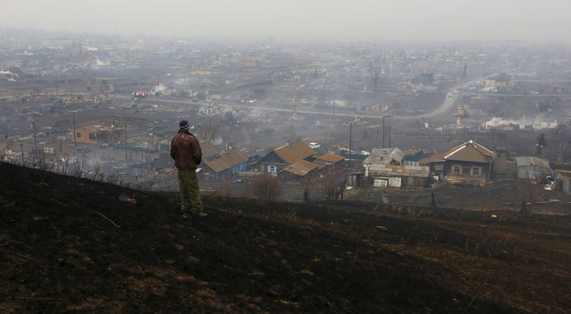 A man looks downhill at the settlement of Shyra, damaged by recent wildfires, in Khakassia region, April 13, 2015. Wildfires in the Russian region of Khakassia in southern Siberia have killed 15 people and caused damage worth at least $96 million, the region's leader said on Monday. (Photo by Ilya Naymushin/Reuters)