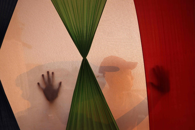 A Palestinian child is silhouetted behind a palestinine flag in a tent on gaza beach in Gaza City on August 1, 2021. (Photo by Mohammed Abed/AFP Photo)