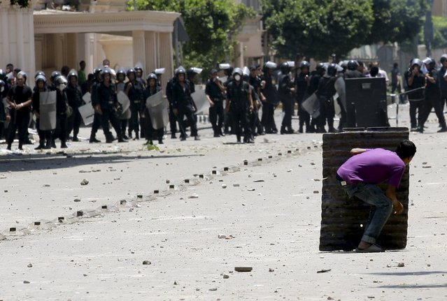A protester takes cover during clashes with riot police in front of the Interior Ministry in Cairo, in this June 29, 2011 file photo. (Photo by Mohamed Abd El-Ghany/Reuters)