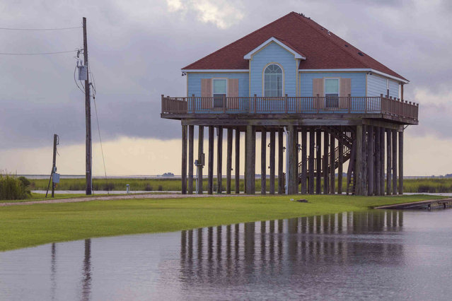 Water begins to rise and cover the land around a lake house by Lake St. Catherine before landfall of Hurricane Ida in New Orleans, Saturday, August 28, 2021. Lake Catherine is outside the levee protection system of New Orleans and has a mandatory evacuation order. (Photo by Matthew Hinton/AP Photo)