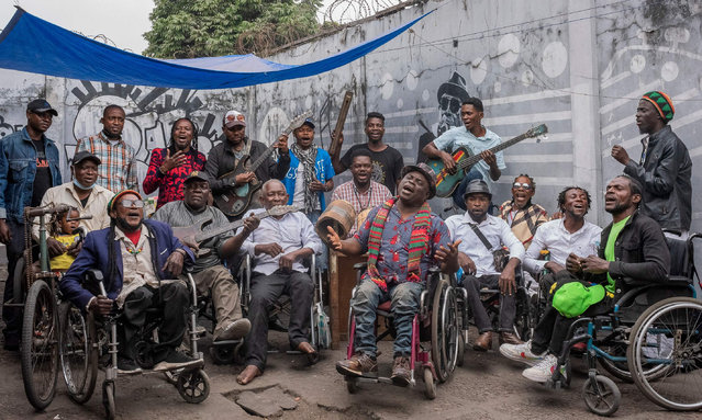 The members of Staff Benda Bilili pose for a group photo during a rehearsal in the popular district of N'djili, Kinshasa, on August 11, 2021. Ten years after their glory days, Staff Benda Bilili dream of returning to the limelight and claim all the fruits of their former success, even if it means falling out with those who made them known In the early 2010s, these penniless, disabled Congolese musicians, living on the streets and riding around in outdated wheelchairs, had turned roumba upside down, set European venues ablaze and wowed the Cannes Film Festival. (Photo by Arsene Mpiana/AFP Photo)
