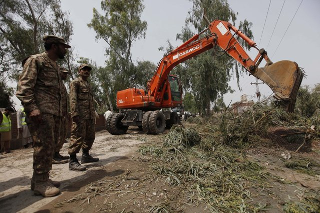 Pakistani army soldiers remove debris from houses that collapsed following torrential rains in Peshawar, Pakistan, 27 April 2015. Rescue workers were scrambling to reach dozens of people believed trapped under collapsed buildings on 27 April after heavy overnight rains and strong winds killed 44 people in north-western Pakistan. (Photo by Bilawal Arbab/EPA)