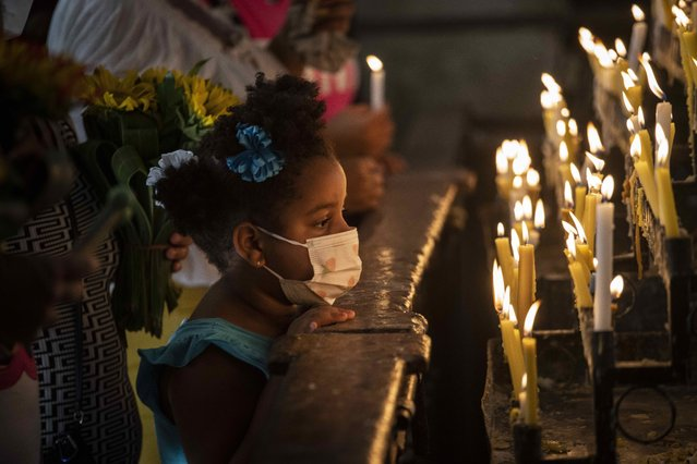 A girl wearing a mask amid the COVID-19 pandemic kneels in prayer before candles at Our Lady of Cobre Church as faithful mark the feast day of Cuba's patron saint, the Virgin of Charity of Cobre, in Havana, Cuba, Wednesday, September 8, 2021. For the second year in a row, the annual procession with the statue of the Virgin of Charity of Cobre was cancelled due to the pandemic. (Photo by Ramon Espinosa/AP Photo)