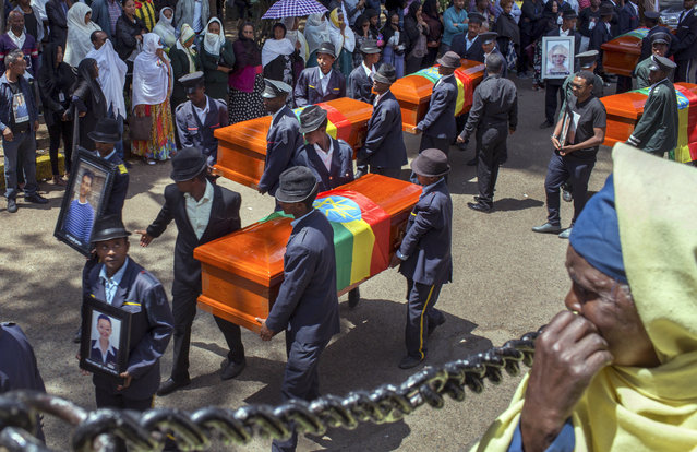 Relatives grieve next to empty caskets draped with the national flag at a mass funeral at the Holy Trinity Cathedral in Addis Ababa, Ethiopia Sunday, March 17, 2019. Thousands of Ethiopians have turned out to a mass funeral ceremony in the capital one week after the Ethiopian Airlines plane crash. Officials have begun delivering bags of earth to family members of the 157 victims of the crash instead of the remains of their loved ones because the identification process is going to take such a long time. (Photo by Mulugeta Ayene/AP Photo)