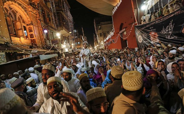 Dawoodi Bohra Muslims raise their arms as they take blessings from their new spiritual leader Syedna Mufaddal Saifuddin in Mumbai February 19, 2014. (Photo by Danish Siddiqui/Reuters)