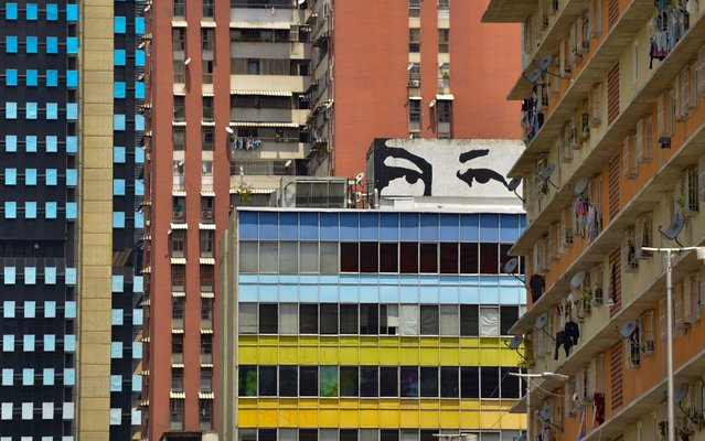 View of a mural depicting late Venezuelan President Hugo Chavez in Caracas, on March 10, 2019. Sunday is the third day Venezuelans remain without communications, electricity or water, in an unprecedented power outage that already left 15 patients dead and threatens with extending indefinitely, increasing distress for the severe political and economic crisis hitting the oil-rich South American nation. (Photo by Matias Delacroix/AFP Photo)