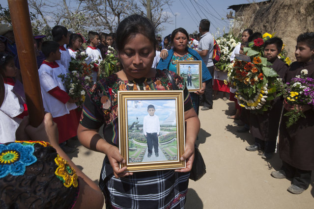 Relatives take part in a burial service holding portraits of Carlos Daniel Xiquin, 10, front, and Oscar Armando Toc Cotzajay, 11, who were kidnapped over the weekend and then killed when family could not raise the ransom money, in Ajuix, Guatemala, Tuesday, February 14, 2017. Authorities found the bodies of the two boys on Sunday, stabbed and thrown into sacks in the municipality of San Juan Sacatepéquez, northwest Guatemala. (Photo by Moises Castillo/AP Photo)