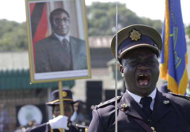 A police officer shouts orders during the Presidential Graduation ceremony which was attended by President Robert Mugabe, pictured in poster in the background,  at the General Police headquarters, in Harare, Zimbabwe, Thursday, May 14, 2015. A total of 698 police officers graduated at the ceremony after undergoing training by the Zimbabwe Republic police. (Photo by Tsvangirayi Mukwazhi/AP Photo)