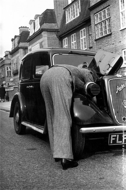 1941: This woman enjoys the practicality of the new fashionable trousers for ladies leaning into the bonnet of her Austin motor car