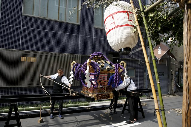 A man prepares a portable shrine for its parade during the Sanja Matsuri festival in the Asakusa district of Tokyo May 17, 2015. (Photo by Thomas Peter/Reuters)