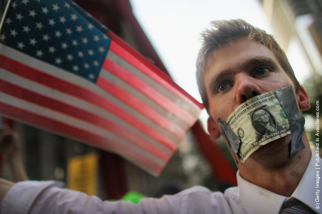 A protester wears a dollar bill over his mouth at the start of a march by demonstrators opposed to corporate profits on Wall Street