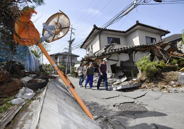 Residents walk past a house damaged by a magnitude-6.5 earthquake in Mashiki, Kumamoto prefecture, southern Japan, Friday, April 15, 2016. (Photo by Yu Nakajima/Kyodo News via AP Photo)