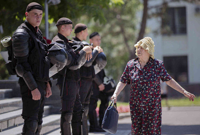 An elderly woman walks by a line of riot policemen standing outside the government headquarters in Chisinau, Moldova, Wednesday, June 12, 2019. Moldova's police chief on Wednesday dismissed six officers who publicly backed a rival government, reflecting a continuing power struggle that has heightened political tensions in the impoverished ex-Soviet nation.(Photo by Roveliu Buga/AP Photo)
