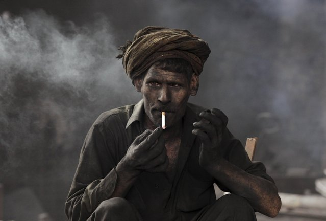 A worker takes a break from his work at a steel smelting plant in Lahore, Pakistan, April 30, 2015. (Photo by Mohsin Raza/Reuters)