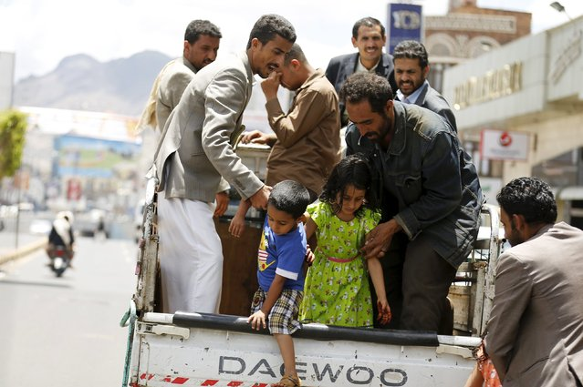People help children step out of a truck taxi in Yemen's capital Sanaa May 6, 2015. (Photo by Khaled Abdullah/Reuters)