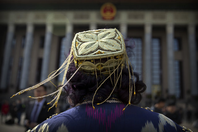 In this Saturday, March 11, 2017 photo, tassels on the hat of an ethnic minority delegate blow in the breeze as she arrives for a plenary session of the Chinese People's Political Consultative Congress (CPPCC) at the Great Hall of the People in Beijing. The annual session of China's ceremonial legislature is designed to awe onlookers with its size and sweep, with nearly 3,000 delegates and hordes of journalists and others gathered in the cavernous auditorium of the hulking Great Hall of the People, itself adjacent to the vast expanse of Tiananmen Square in the heart of the Chinese capital. Yet the experience is also made up of tiny moments, details that point to the personalities of the participants and the event's unique, sometimes quirky, traits that a casual observer might easily miss. Delegates attend in all their finery, whether smart business suits, crisply pressed military uniforms or a monk's maroon robes. The various minority ethnic costumes featuring elaborate silver headdresses and embroidered silks liven up the scene with splashes of color and the tinkle of bells. On the way to their seats, they rub shoulders with one another and the army of white-gloved attendants in black suit and tie, ever ready to check an identification card or pour a cup of steaming hot tea. For many, the 10-day session is a chance not only to perform their pre-ordained tasks of discussing and approving government reports and any pieces of legislation before the body, but also to catch up on news and see old friends, particularly those from other parts of the vast nation of 1.37 billion people. Selfies are now de rigueur for attendees, alongside the standard group photo beneath azure skies freed from the usual choking smog, reportedly through the temporary closure of polluting industries in the surrounding region. (Photo by Mark Schiefelbein/AP Photo)