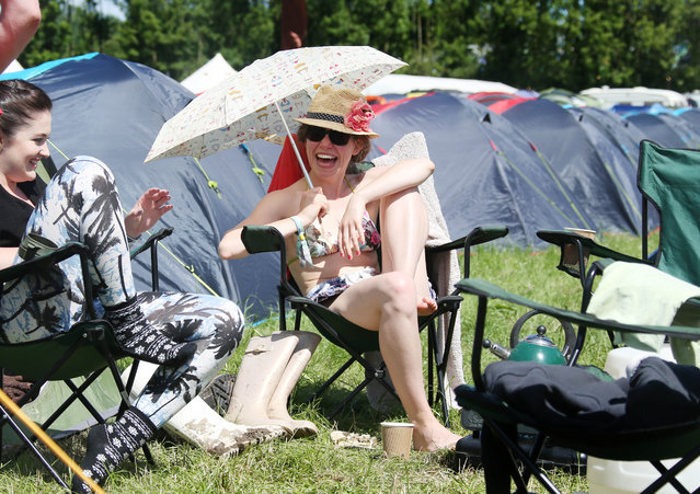 A festival goer shelters from the sun under an umbrella amongst tents during Glastonbury Music Festival on Saturday, June 27, 2015 at Worthy Farm, Glastonbury, England. (Photo by Joel Ryan/Invision/AP Photo)