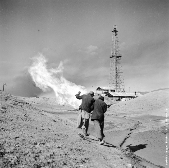 1954: Shielding themselves from the far-reaching heat of a burning oil well, two Iranian National Oil Company workers rush across the fields of the Iranian countryside