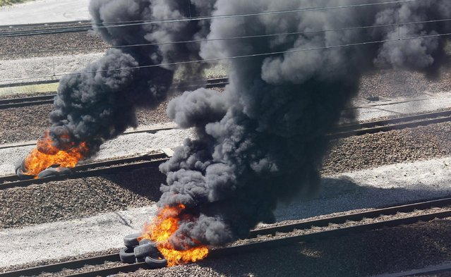 Striking workers invade the Eurotunnel train tracks in Calais, northern France, and burn tires in a protest against job cuts, Tuesday, June 30, 2015. About 100 striking French ferry workers have blocked train traffic between France and England for a second time in a week. Both freight companies and Eurostar said they were suspending train services on Tuesday after the workers blocked the tracks in the French port city of Calais. (Photo by Michel Spingler/AP Photo)