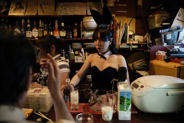 A bartender, in costume, prepares a drink for a patron in a bar at the Golden Gai in the Shinjuku district of Tokyo, July 26, 2019. (Photo by Jae C. Hong/AP Photo)