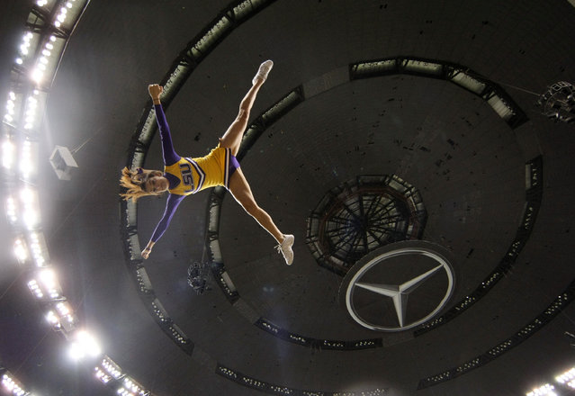 An LSU cheerleaders is flipped before the BCS National Championship college football game against Alabama Monday, January 9, 2012, in New Orleans. (Photo by Gerald Herbert/AP Photo)