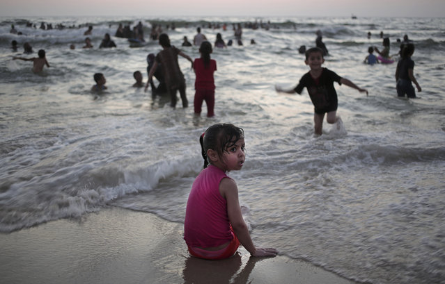 In this June 16, 2015 photo, Palestinians enjoy a summer day on the beach of Gaza City. (Photo by Khalil Hamra/AP Photo)
