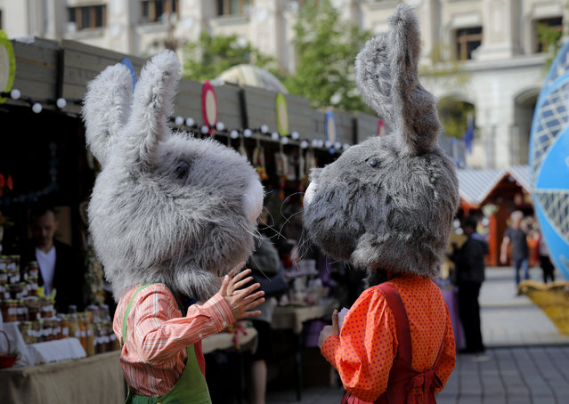 In this Thursday, April 13, 2017, picture entertainers wearing rabbit costumes speak at a fair in Bucharest, Romania. Ahead of Easter, celebrated by both Orthodox and Catholic believers on April 16 processions of priests clad in golden robes carrying foliage on Palm Sunday in a recreation of Jesus' ride into Jerusalem, mixed with more commercial flavored celebrations like an Easter fair outside the giant palace built by late Communist leader Nicolae Ceausescu where entertainers strutted around wearing giant rabbit heads. (Photo by Vadim Ghirda/AP Photo)