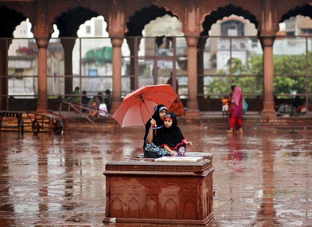 Muslims girls sit on a plinth before offering Friday prayers as it rains at the Jama Masjid (Grand Mosque) during the holy month of Ramadan in the old quarters of Delhi, India, July 10, 2015. (Photo by Anindito Mukherjee/Reuters)