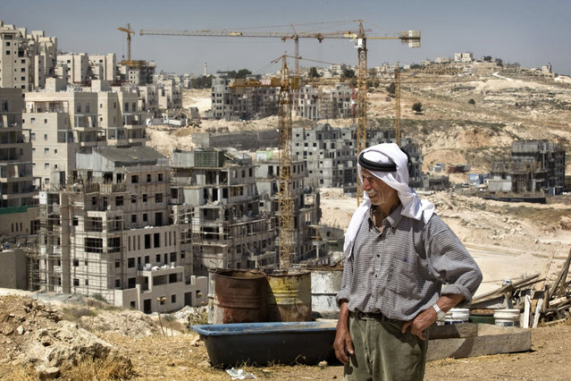 In this June 3, 2009 file photo, Palestinian Said Eid stands next to his house, not seen, as construction continues on a new housing development in the Jewish neighborhood of Har Homa in east Jerusalem, background. As Israeli Prime Minister Benjamin Netanyahu becomes Israel's longest-serving prime minister, he is solidifying his place as the country's greatest political survivor and the most dominant force in Israeli politics in his generation. (Photo by Sebastian Scheiner/AP Photo/File)