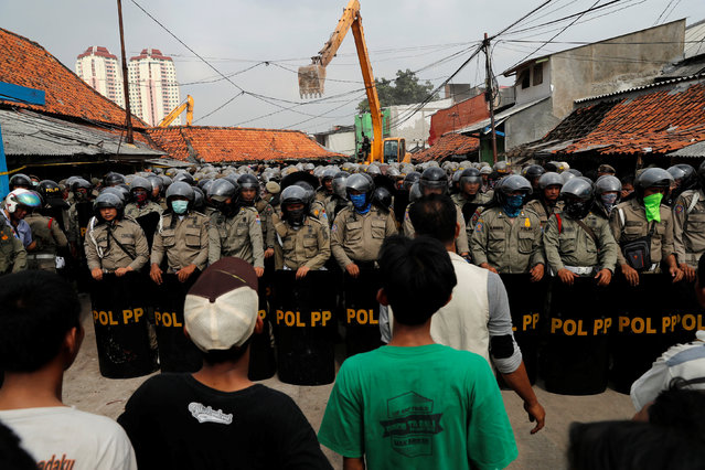Residents stand opposite civil service policemen before an eviction as machinery demolishes illegal houses at Luar Batang fisheries village in Jakarta,  Indonesia, April 11, 2016. (Photo by Reuters/Beawiharta)