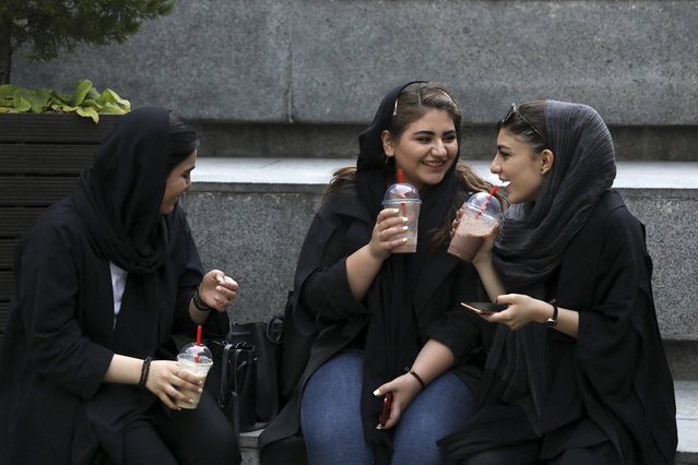 In this Tuesday, July 2, 2019 photo, youngsters spend an afternoon while siting on steps outside a shopping mall in northern Tehran, Iran. A few daring women in Iran's capital have been taking off their mandatory headscarves, or hijabs, in public, risking arrest and drawing the ire of hard-liners. Many others stop short of outright defiance and opt for loosely draped scarves that show as much hair as they cover. More women are pushing back against the dress code imposed after the 1979 Islamic Revolution, and activists say rebelling against the hijab is the most visible form of anti-government protest in Iran today. (Photo by Vahid Salemi/AP Photo)