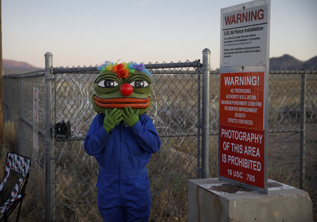 "Martin Custodio wears a Pepe mask while standing near razor wire at an entrance to the Nevada Test and Training Range near Area 51, Friday, September 20, 2019, near Rachel, Nev. People came to visit the gate inspired by the ""Storm Area 51"" internet hoax. (Photo by John Locher/AP Photo)"