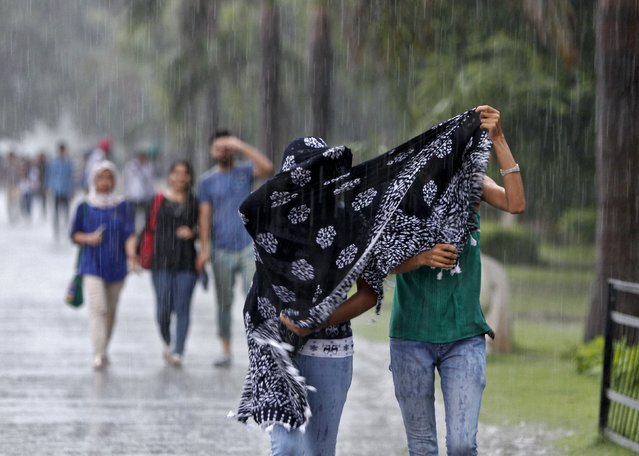 Girls try to cover themselves by a stole during a heavy rain shower in Chandigarh, India, July 10, 2015. (Photo by Ajay Verma/Reuters)