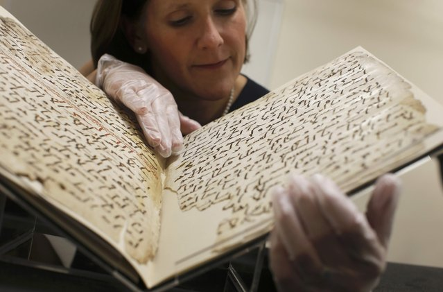Conservator, Marie Sviergula holds a fragment of a Koran manuscript in the library at the University of Birmingham in Britain July 22, 2015. (Photo by Peter Nicholls/Reuters)