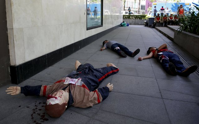 Employees pretending to be victims, lie on a pavement, together with a mannequin,  during an earthquake drill in Taguig, Metro Manila in the Philippines July 23, 2015. (Photo by Erik De Castro/Reuters)