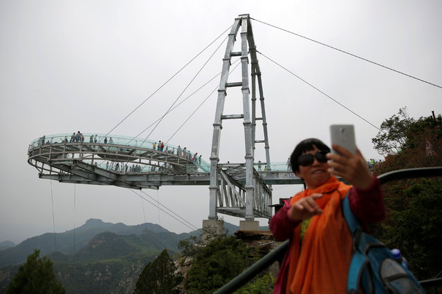 A woman takes a selfie in front the glass sightseeing platform on Shilin Gorge in Beijing, China, May 27, 2016. (Photo by Kim Kyung-Hoon/Reuters)
