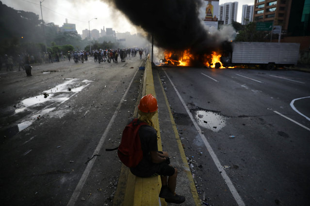A demonstrator rests near burning trucks while rallying against President Nicolas Maduro in Caracas, Venezuela, May 27, 2017. (Photo by Carlos Barria/Reuters)