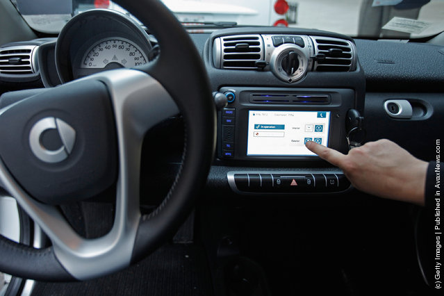 A car2go empoloyee demonstrates how members use the built-in touchscreen to access the car during a press preview
