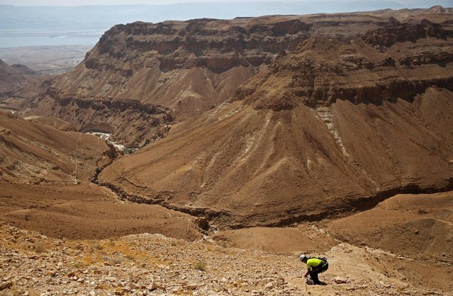 A volunteer with the Israeli Antique Authority holds a securing rope as he walks down to enter the Cave of the Skulls, an excavation site in the Judean Desert near the Dead Sea, Israel June 1, 2016. (Photo by Ronen Zvulun/Reuters)