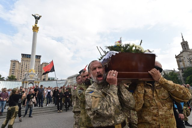Fighters of Ukrainian volonteers battalion of Right Sector carry coffins with the bodies of their friends  Yuriy Gnatyuk and Robert Masley, died as a result of pro-Russian separatists shelling in Donetsk region,during the funeral ceremony on Independence Square in Kiev on June 14, 2016. (Photo by Sergei Supinsky/AFP Photo)