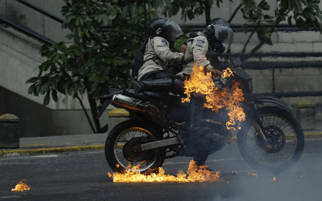 Police hit by a fire bomb thrown by anti-government protesters get off their bike to put out the flames, during a 12-hour national sit-in, in Caracas, Venezuela, Monday, June 5, 2017. Anti-government protesters shut down main roads to demand new presidential elections after the release of a video in which jailed Venezuela opposition leader Leopoldo Lopez expressed support for the movement. (Photo by Fernando Llano/AP Photo)