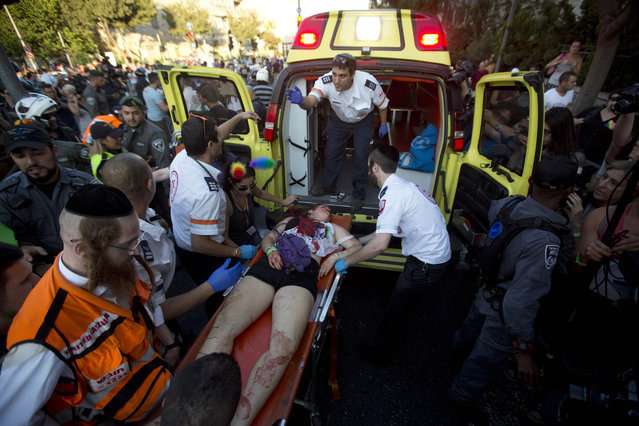 Paramedics roll a wounded person into ambulance after an ultra-Orthodox Jew attacked people with a knife during a Gay Pride parade Thursday, July 30, 2015 in central Jerusalem. (Photo by Sebastian Scheiner/AP Photo)