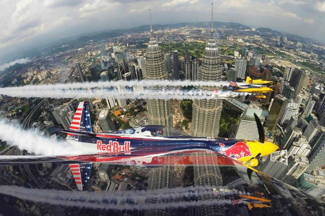 Kirby Chambliss of the U.S. flies in formation with Matt Hall of Australia, Yoshihide Muroya of Japan and Nigel Lamb of Britain prior to the third stage of the Red Bull Air Race World Championship in front of the Petronas Towers in Kuala Lumpur May 15, 2014. (Photo by Joerg Mitter/Red Bull handout via Reuters)