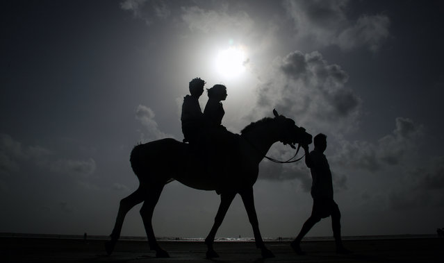 Indian couple silhouetted against the sky enjoy a horse ride along the Arabian Sea coast in Mumbai, India, 25 June 2014. The India Meteorological Department (IMD) has predicted below average rains for the monsoon season which runs from June to September and that accounts for about 80 percent of India's annual rainfall. (Photo by Divyakant Solanki/EPA)