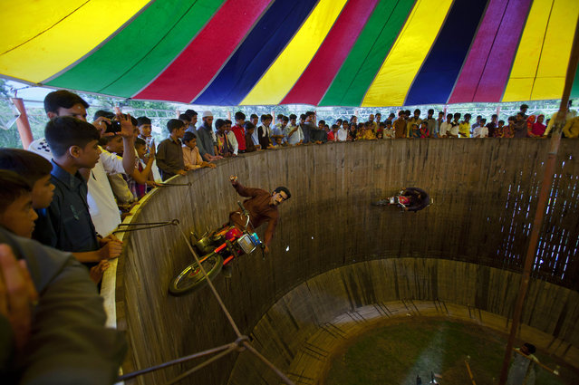 "Pakistanis watch two performers demonstrate their motorcycle skills inside the ""well of death"" at a fair set up for the occasion of the Eid al-Fitr holiday in Rawalpindi, Pakistan, Saturday, July 18, 2015. (Photo by Anjum Naveed/AP Photo)"