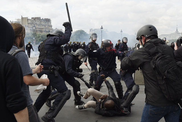 Police officers clash with a demonstrator near the Invalides during a protest against proposed labour reforms in Paris on June 14, 2016. Strikes closed the Eiffel Tower and disrupted transport in France on June 14 as tens of thousands prepared to march against labour reforms with the Euro 2016 football championship in full swing. (Photo by Dominique Faget/AFP Photo)